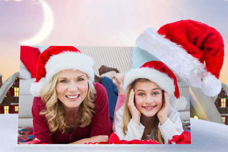 female christmas: Festive little girl with mother surrounded by gifts against cute christmas village under crescent moon