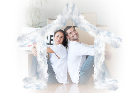 mortage: Happy young couple sitting on the floor against house outline in clouds Stock Photo
