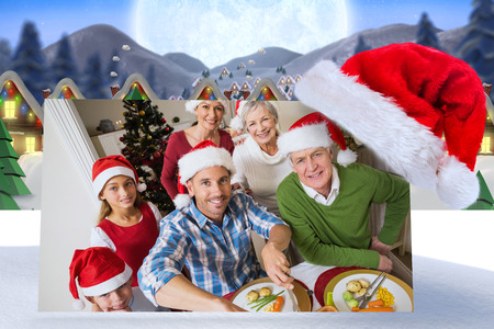 quaint: Father in santa hat carving chicken at christmas dinner against quaint town with bright moon