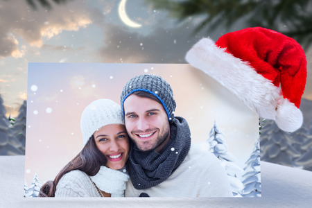 north pole: young winter couple against cute christmas village at north pole