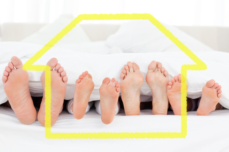 straight up: Composite image of feet in bed pointing straight up against house outline Stock Photo