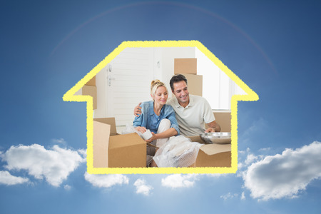 unpacking: Smiling couple unpacking boxes in a new house against cloudy sky with sunshine