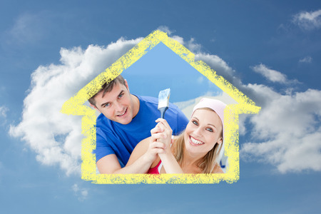 Hugging couple having fun while painting a room against cloudy sky