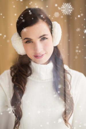 ear muffs: Pretty brunette with ear muffs smiling at camera against snow falling Stock Photo