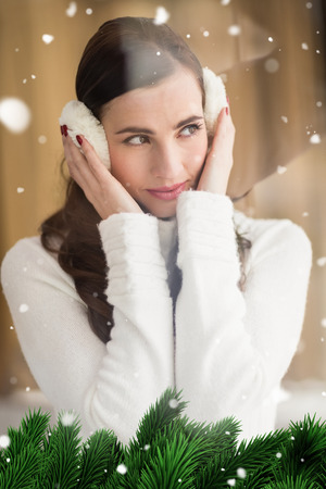 ear muffs: Pretty brunette with ear muffs thinking against green fir branches with snow Stock Photo