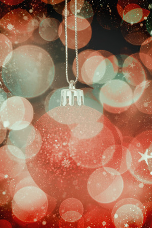 red glittery: Snow falling against twinkling red and orange lights Stock Photo