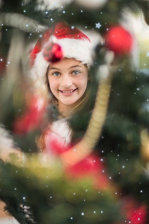 decorating christmas tree: Festive litte girl decorating christmas tree against snow falling Stock Photo