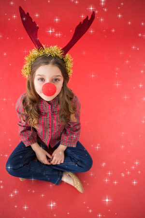 red nose: Festive little girl wearing red nose against twinkling stars Stock Photo