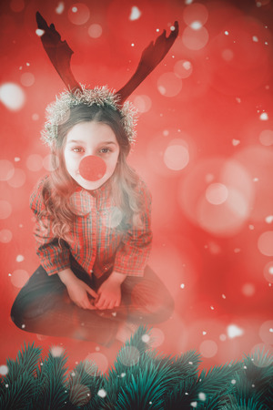 nariz roja: Festive little girl wearing red nose against digitally generated twinkling light design Foto de archivo