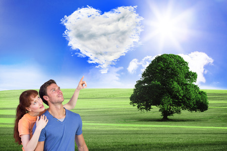 looking upwards: Happy couple looking upwards against cloud heart Stock Photo