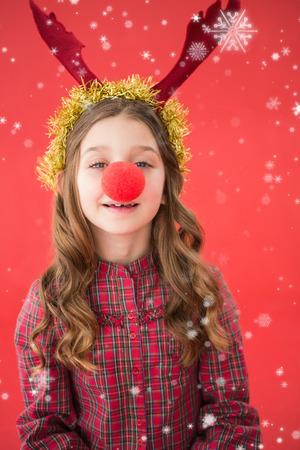 nariz roja: Niña festiva que desgasta la nariz roja contra la nieve que cae
