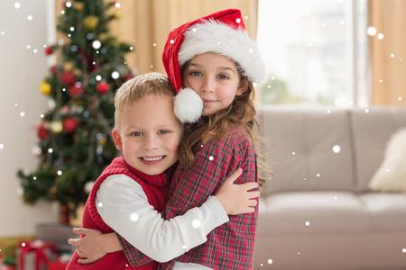 siblings: Festive siblings smiling at camera against snow