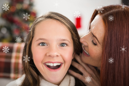 telling: Mother telling her daughter a christmas secret against snowflakes