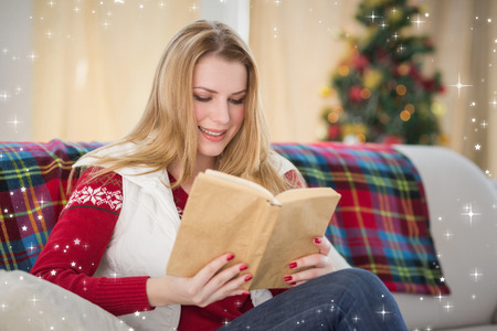 christmas time: Pretty blonde reading book at christmas time against twinkling stars