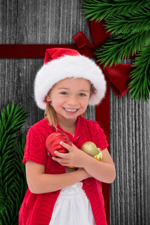 wearing santa hat: Cute little girl wearing santa hat holding baubles against wood with festive bow Archivio Fotografico