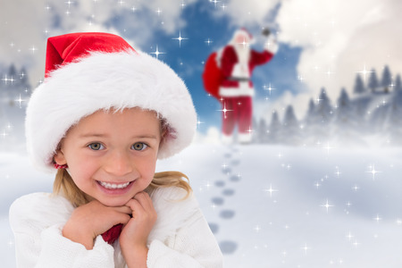 wearing santa hat: Cute little girl wearing santa hat  against blue sky with white clouds