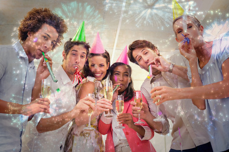 party poppers: Business people celebrating at the workplace with glasses of champagne against colourful fireworks exploding on black background