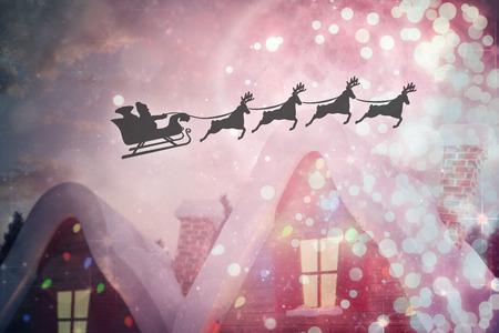 papa noel en trineo: Silueta de Pap� Noel y renos en contra del pueblo lindo navidad Foto de archivo