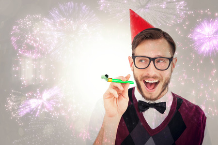 cheesy grin: Geeky hipster in party hat with horn against colourful fireworks exploding on black background