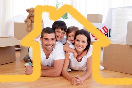 descansando: La familia feliz después de comprar casa nueva contra la casa de esquema Foto de archivo