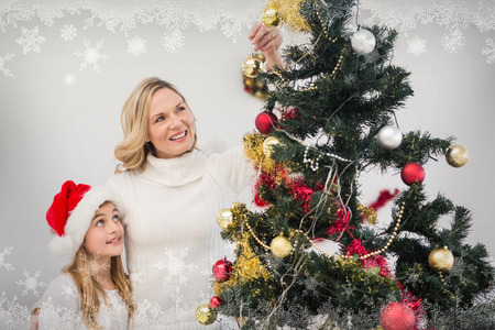 decorating christmas tree: Festive mother and daughter decorating christmas tree against snowflake frame