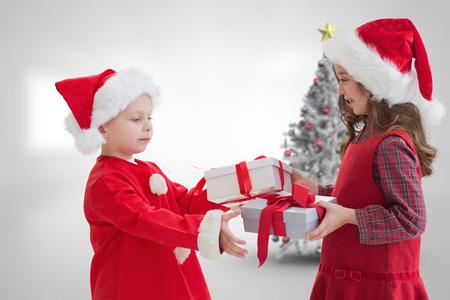 siblings: Cute siblings with gifts against christmas tree in bright room