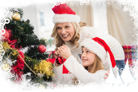 decorating christmas tree: Festive mother and daughter decorating christmas tree against frost frame
