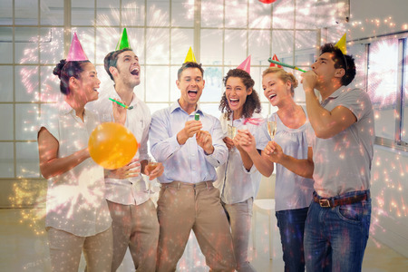 party poppers: Casual business team celebrating with champagne and party poppers against colourful fireworks exploding on black background