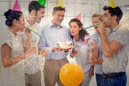 coworkers: Casual businessmen team celebrating a birthday against colourful fireworks exploding on black background Stock Photo