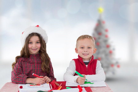 siblings: Cute siblings drawing pictures against blurry christmas tree in room Stock Photo