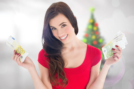 Cheerful brunette holding her cash money  against blurry christmas tree in room