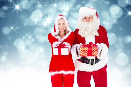 se�ora: Santa y se�ora Claus sonriendo a la c�mara regalo de ofrecimiento contra el dise�o de luz brillante en azul