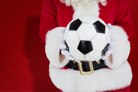 mid section: Mid section of santa holding football against red snowflake background