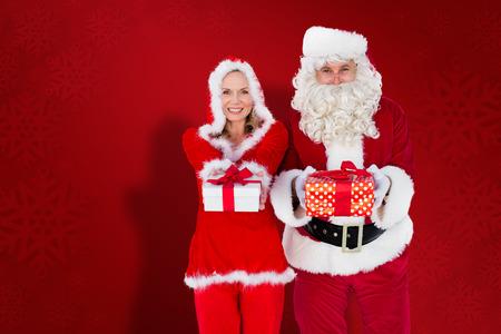 mrs: Santa y se�ora Claus sonriendo a la c�mara ofrecer regalo contra el fondo del copo de nieve de color rojo Foto de archivo