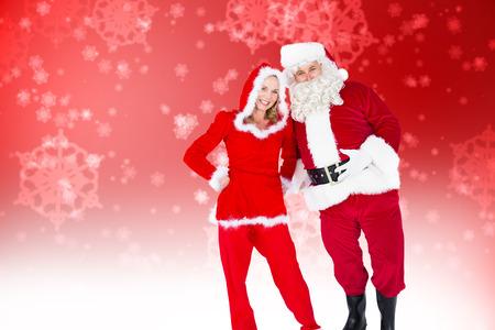 señora: Santa y señora Claus sonriendo a la cámara contra el diseño del copo de nieve delicada generada digitalmente