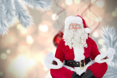 Santa claus sitting in lotus pose  against digital hanging christmas bauble decoration