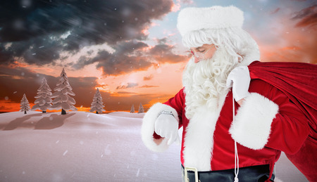 checking time: Festive santa claus checking time against snowy landscape with fir trees Stock Photo
