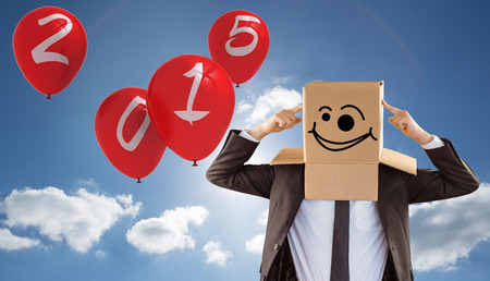 wonky: Anonymous businessman pointing to box against cloudy sky with sunshine Stock Photo