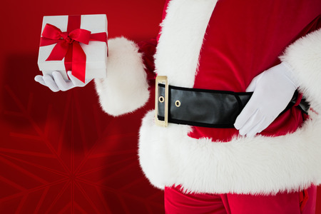 mid section: Mid section of santa holding gift against red snowflake background Stock Photo