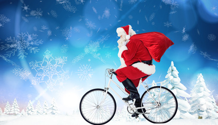 Santa claus delivering gifts with bicycle against snowy landscape with fir trees