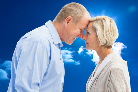 facing each other: Happy mature couple facing each other against bright blue sky with clouds Stock Photo