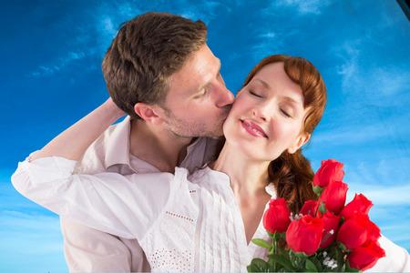 mujer con rosas: Mujer que consigue rosas del hombre contra el cielo azul con nubes blancas