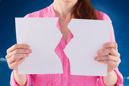 strife: Woman holding torn sheet of paper against cloudy sky with sunshine