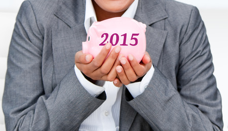 corporate greed: Close up of a smiling businesswoman holding a piggybank  against 2015 in grey