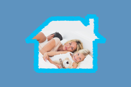 cuddly toy: Family lying together on a bed against blue background with vignette