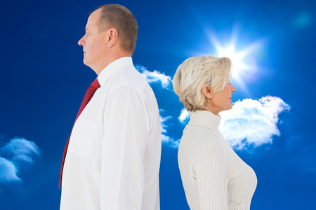 facing each other: Older couple standing not facing each other against bright blue sky with clouds Stock Photo