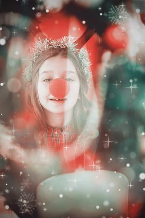 nariz roja: Niña festiva que desgasta la nariz roja contra vela encendida contra fondo festivo