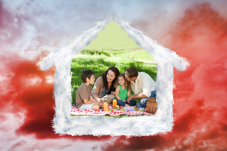 picnicking: Family picnicking together against green grass under red cloudy sky