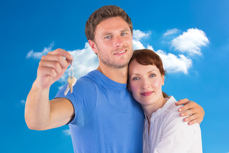 cloudy home: Couple holding keys to home against cloudy sky