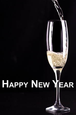 champaigne: Happy new year against glass of champaigne being filled Stock Photo